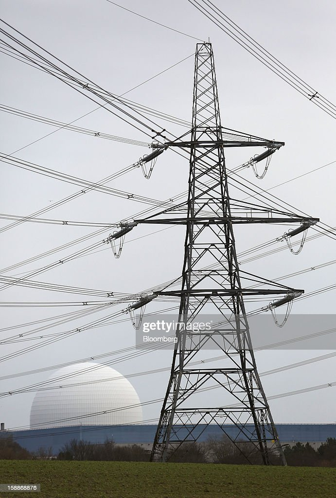Power transmission lines hang from an electricity pylon near the reactor dome of Sizewell B nuclear power station, operated by Electricite de France SA (EDF), in Sizewell, U.K., on Wednesday, Jan. 2, 2013. EDF operates eight U.K. atomic power stations and has proposed to add Areva reactors at its Hinkley Point and Sizewell sites. Photographer: Chris Ratcliffe/Bloomberg via Getty Images