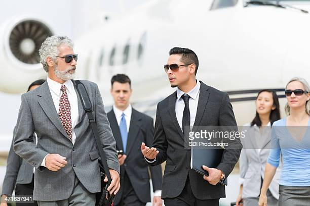 Powerful business team deboarding private corporate jet