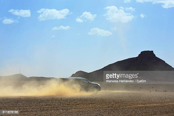 Powerful land vehicle in motion on a deserted dusty ground