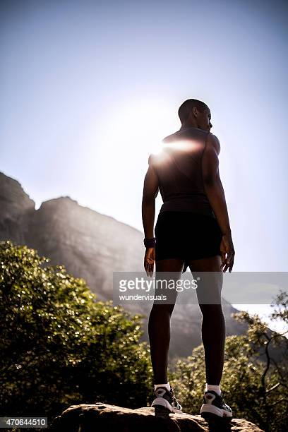 Powerful male athlete standing atop a mountain