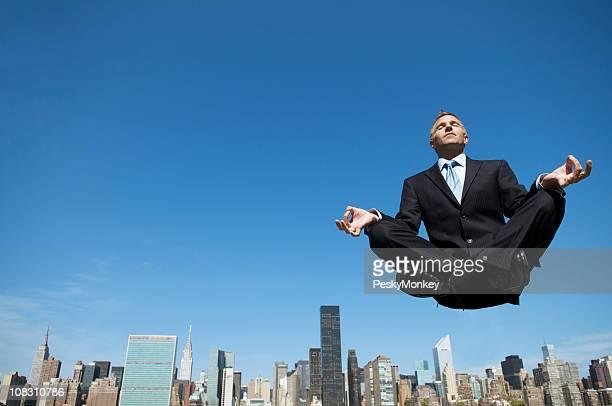 Potente empresario Meditando Levitating por encima de los edificios de la ciudad