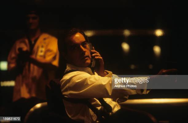 Powers Boothe holds a phone in a scene from the film 'Sudden Death' 1995