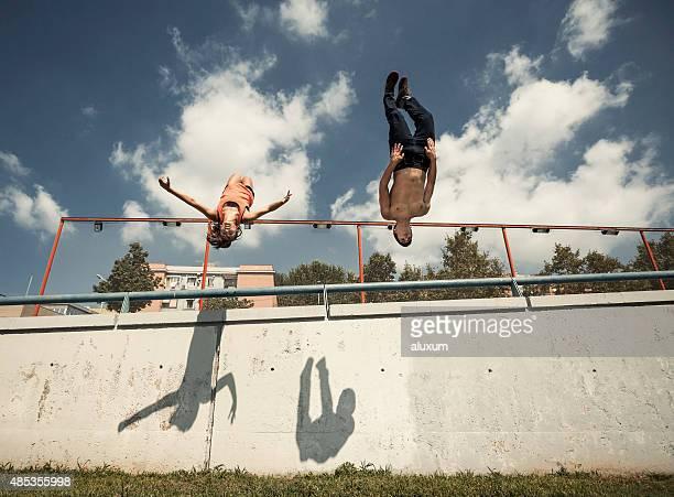 Üben parkour- in der Stadt Frau und Mann einen Salto rückwärts