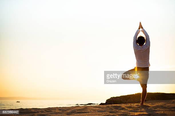 Üben yoga und meditation im Sommer am Strand bei Sonnenuntergang