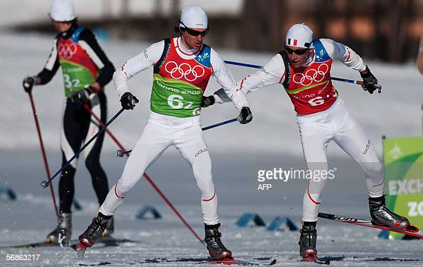Francois Braud of France switches with his teammate Ludovic Roux at the 2006 Winter Olympics' Nordic Combined team 4x5 km in Pragelato 16 February...