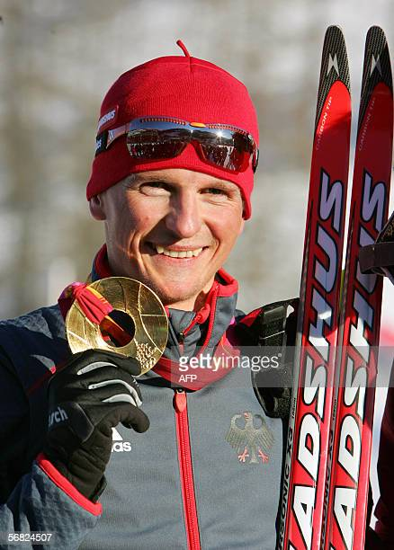 Germany's Georg Hettich holds his gold medal after winning the Individual Gundersen 15 km during the 2006 Winter Olympic Games' Nordic Combined in...