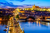 Prague, Czech Republic. Charles Bridge and Hradcany (Prague Castle) with St. Vitus Cathedral and St. George church evening dusk, Bohemia landmark in Praha.