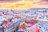 Prague down town center at winter Christmas time, classical view on snowy roofs in central part of city.
