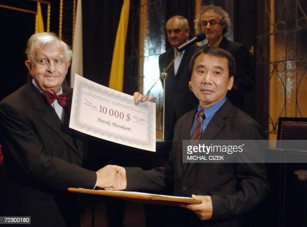 Japanese writer Haruki Murakami shakes hands with Kurt Krolop German professor of literature and director of Franz Kafka Society as he receives the...