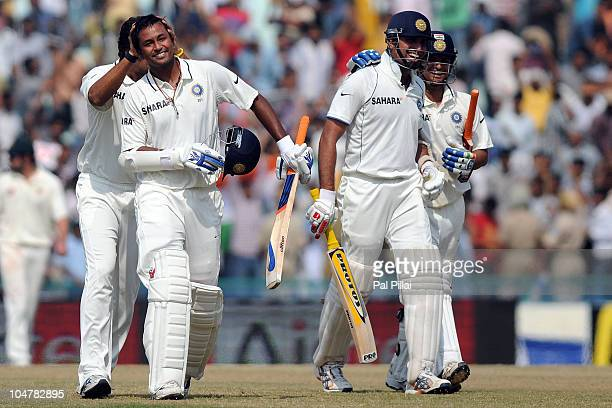 Pragyan Ojha of India is congratulated by teammate Murali Vijay as VVS Laxman and Suresh Raina celebrate after their win on day five of the First...