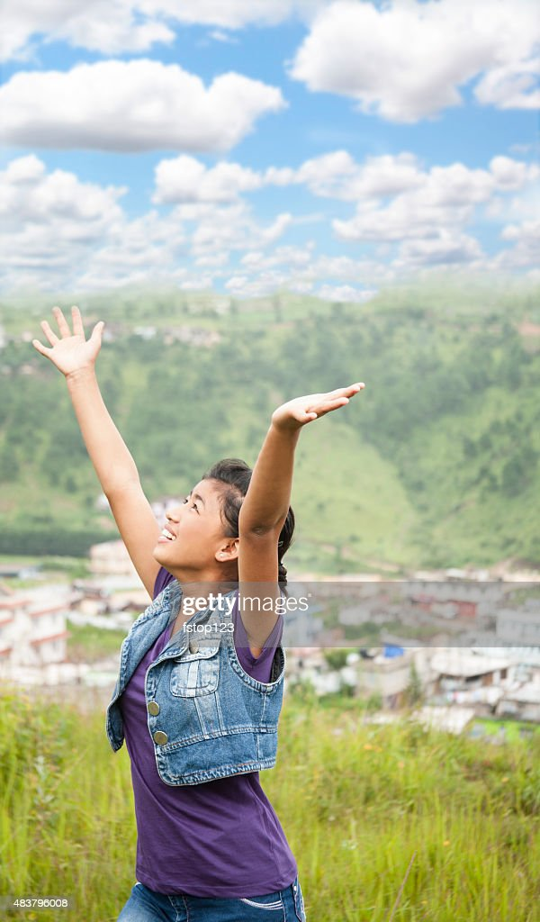Praise! Asian girl gives thanks as she lifts arms upward.