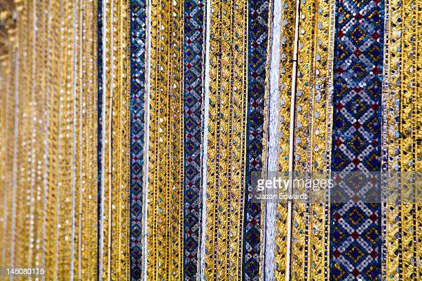 Glass tile mosaic and gold leaf decorate ornate pillars of a temple.