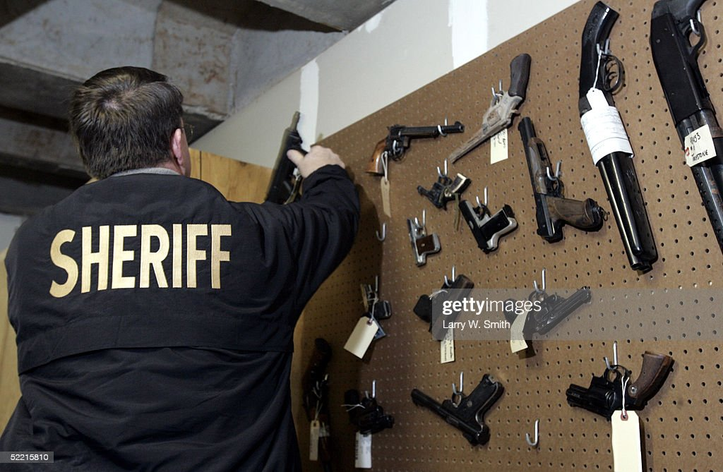 Pratt County Sheriff Vernon Chinn hangs up a gun taken during a meth bust on Febuary 18, 2005 along with other guns in the evidence room at the Pratt County Sheriffs office in Pratt, Kansas. The Pratt County sheriff office has over 700 square acres of rural land to patrol on a daily basis looking for any kind of methamphetamine substances such as trash or labs.