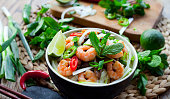 Vietnamese prawn noodle , Tasty traditional  with rice noodles, spring onions, king prawns, bird's eye green, red chilies and shiitake mushrooms. Decorated with piece of fresh lime, leaves of mint, ba