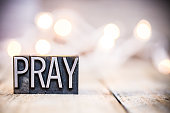 The word PRAY written in vintage metal letterpress type on a bokeh light and wooden background.