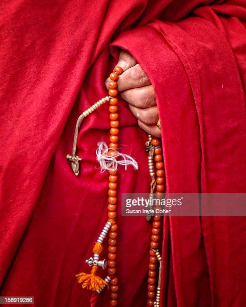 Prayer Beads with a red robed monk , Bhutan