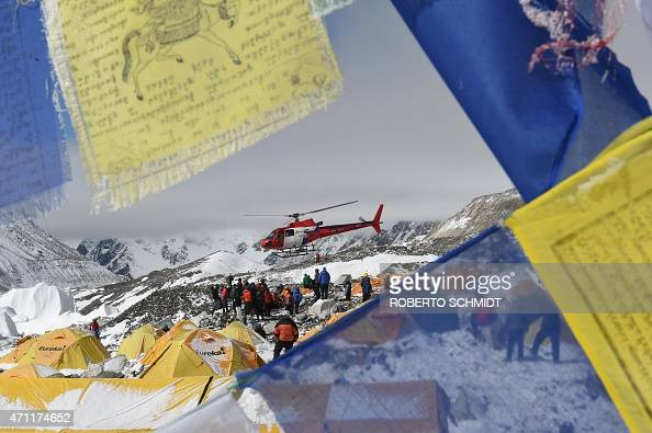 Prayer flags frame a rescue helicopter as it ferries the injured from Everest Base Camp on April 26 a day after an avalanche triggered by an...
