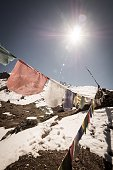 Prayer Flags On Snow Covered Mountain Against Bright Sky