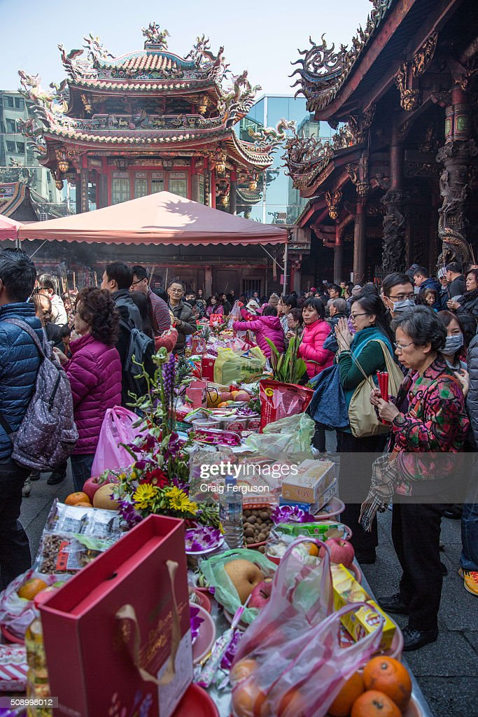 Praying at the offerings table. On the first day of the Chinese lunar year it is traditional to visit temples to light incense and pray for a prosperous year. Thousands come to Longshan Temple, one of the oldest and most important in Taipei every year.
