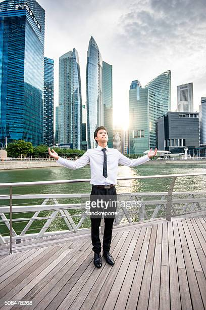 praying business man against the skyscraper in singapore