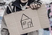 Young homeless man holding sign with painted house