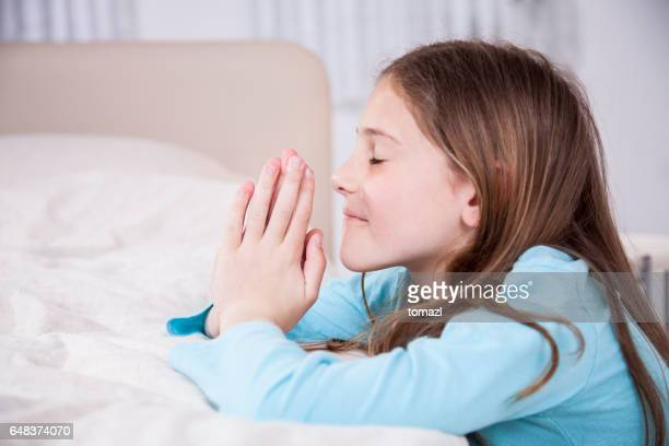 Praying girl at the side of her bed