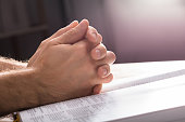 Close-up Of Man's Praying Hands Over The Bible