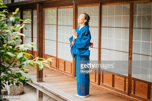 Praying Japanese Woman with Eyes Closed at Temple Kyoto Japan