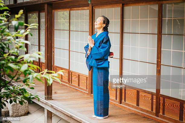 Praying Japanese Woman with Eyes Closed at Temple Kyoto Japan