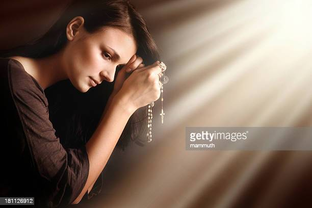Praying young woman in divine light