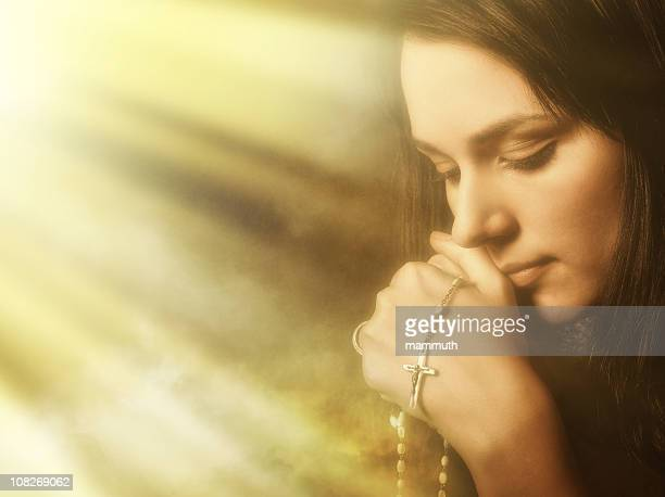 Praying young woman in light and incense smoke