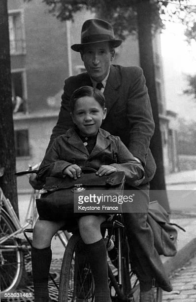 Père conduisant son fils à l'école à vélo le jour de la rentrée des classes en France circa 1945