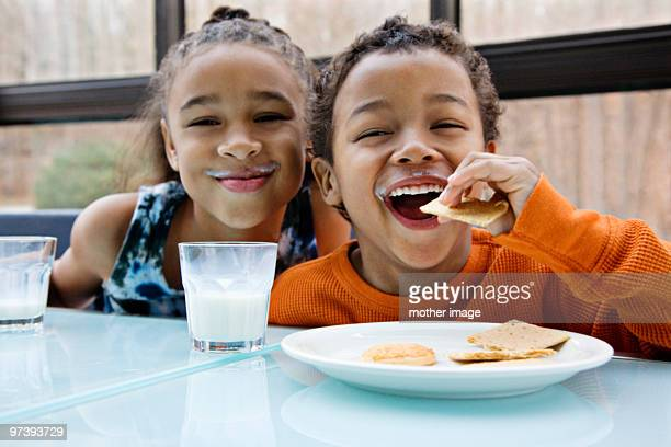 pre teen african american siblings snacking