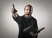 Man dressed as a priest angrily preaching holding the bible in his hand