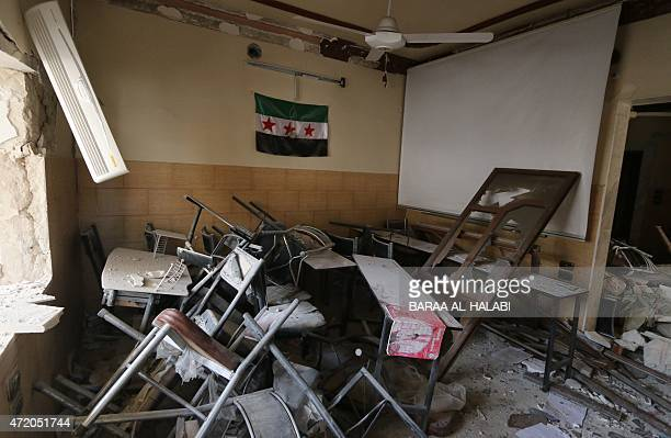 A preBaath Syrian flag now used by the Syrian opposition hangs in a heavily damaged classroom after a barrel bomb hit a school in Syria's northern...
