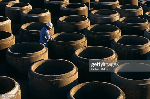 'Precast concrete pipes are prepared for distribution by a Mexicanborn employee at Hanson Pipe Products Grand Prairie Texas USA He cleans and...