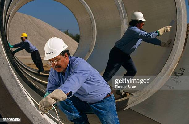 'Precast concrete pipes are prepared for distribution by a Mexicanborn employees at Hanson Pipe Products Grand Prairie Texas USA They are inspcting...