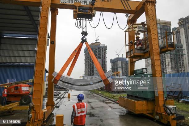 Precast concrete tunnel segments are maneuvered outside by crane at the Mumbai Metro Rail Corp casting yard in Mumbai India on Monday Aug 28 2017 The...