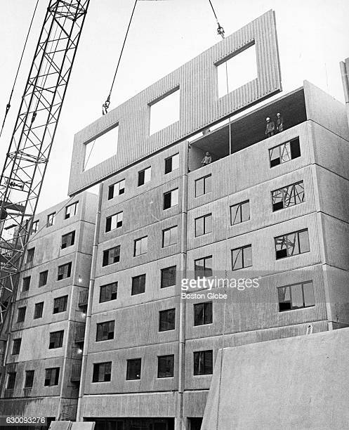 A precast piece of a building is moved into place in the South Cove section of Boston on March 15 1972 Many building projects at this time used...