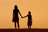 Mother and daughter enjoy watching sunset together.