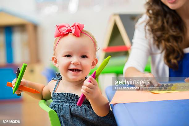 Precious happy toddler girl in preschool playing with crayons