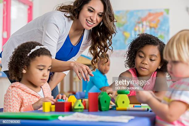 Precious preschool girls playing with building blocks at daycare