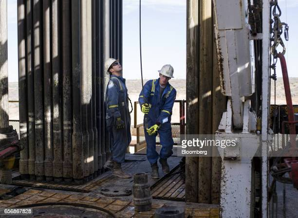 Precision Drilling oil rig operators prepare to install a bit guide on the floor of a Royal Dutch Shell Plc oil rig near Mentone Texas US on Thursday...