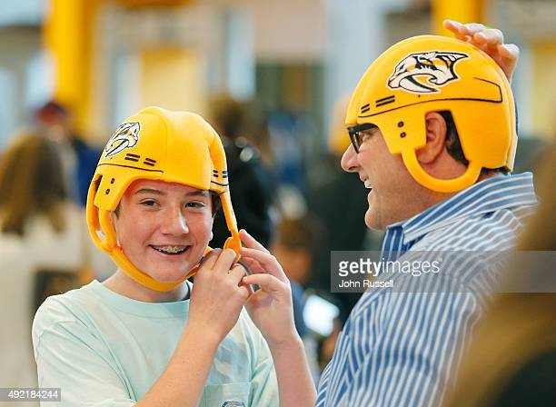Predators fans strap on their Gold foam helmets as they arrive for the Nashville Predators game against the Edmonton Oilers during an NHL game at...
