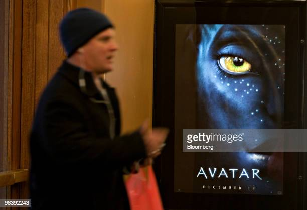 A predestrian walks past a poster advertising the movie 'Avatar' in the lobby of a movie theater in New York US on Wednesday Feb 3 2010 News Corp...