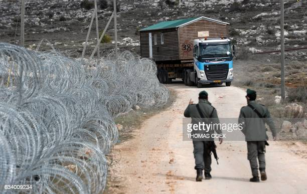 A prefabricated house is transported by a lorry after being are removed from the Israeli Amona wildcat outpost northeast of Ramallah in the occupied...