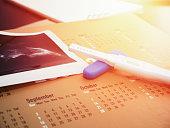 pregnancy test on calendar with ultrasound print background