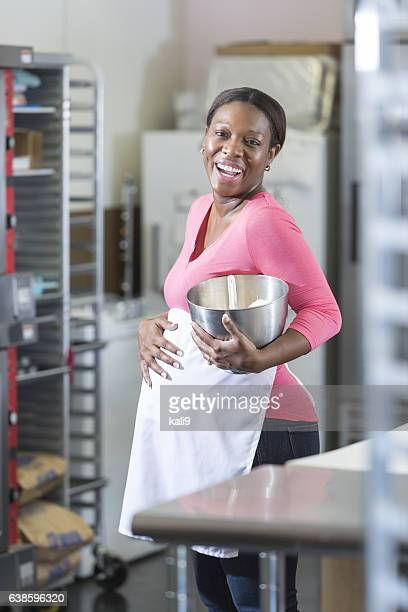 Pregnant, African American woman working in bakery
