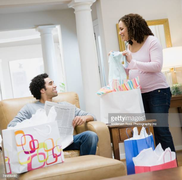 Pregnant African couple looking at baby clothes