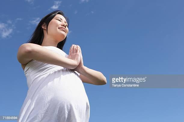 Pregnant Asian woman doing yoga outdoors